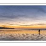 Un pêcheur de vers de vase sur la plage de Ault au pied des falaises