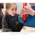 Noémie (enfant,fille, 8 ans) réalise un nichoir pour rouge-gorge dans le cadre des ateliers du festival de l'oiseau. Les planches ont été coupées et préparées par les animateurs. Les enfants sont deux par deux et chaque binôme réalise deux nichoir. Les enfants assemblent et vissent les planches à la visseuse électrique puis ils clouent du shingle sur le toit et découpent celui-ci en biseau à la pince coupante. Saison : Printemps - Lieu : Abbeville, Somme, Picardie, France.