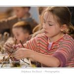 Installation d'un nid dans les branchages - Noémie (enfant,fille, 8 ans) réalise un oiseau en argile dans le cadre des ateliers du festival de l'oiseau. L'oiseau est ensuite décoré avec des matériaux (végétaux) naturels : copeaux, mousse, branchages... Saison : Printemps - Lieu : Abbeville, Somme, Picardie, France.