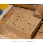 Dessin du contour de l'oiseau au crayon sur la pierre - Noémie (enfant,fille, 8 ans) réalise une sculpture sur pierre dans le cadre des ateliers du festival de l'oiseau. Elle trace le contour de l'oiseau à sculpter au crayon sur la pierre, puis à la pointe à tracer et enfin au ciseau à bois. La pierre est ensuite poncée et les détails ajoutés. Saison : Printemps - Lieu : Abbeville, Somme, Picardie, France.