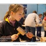 La forme est creusée avec un ciseau à bois plus large. Noémie (enfant,fille, 8 ans) réalise une sculpture sur pierre dans le cadre des ateliers du festival de l'oiseau. Elle trace le contour de l'oiseau à sculpter au crayon sur la pierre, puis à la pointe à tracer et enfin au ciseau à bois. La pierre est ensuite poncée et les détails ajoutés. Saison : Printemps - Lieu : Abbeville, Somme, Picardie, France.