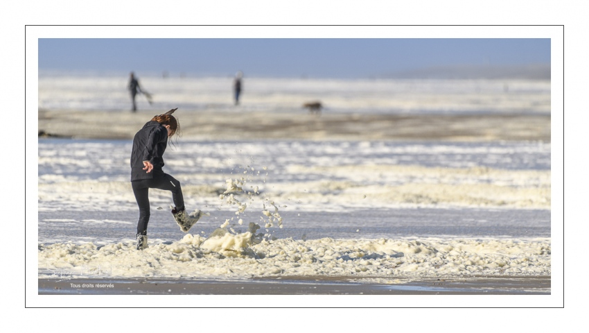 Enfants qui jouent sur la plage avec l'écume de mai