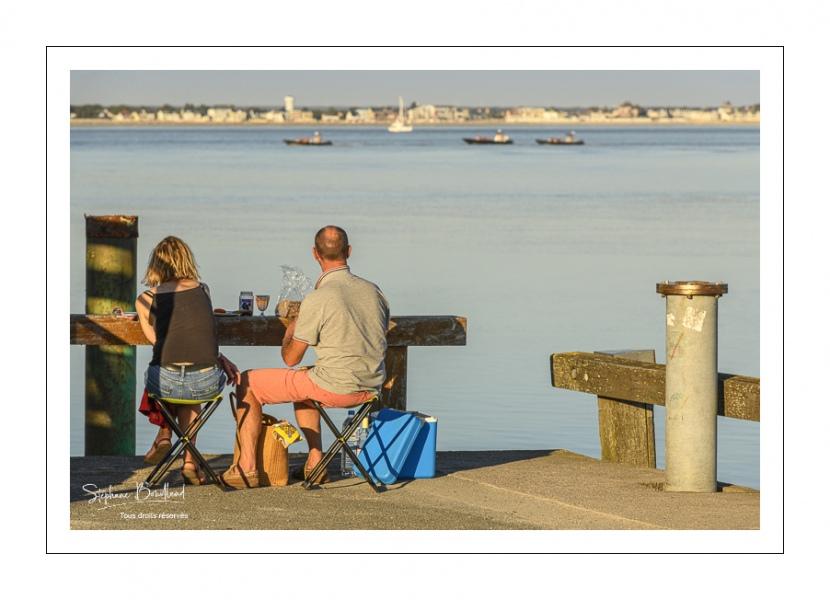 Des touristes pique-niquent devant la baie dans le port du Hourdel