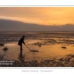 Enfant jouant dans les flaques avec un baton. Saison : hiver - Lieu : Le Crotoy, Baie de Somme, Somme, Picardie, France.