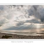 Une fin d'après-midi nuageuse au hâble d'Ault alors qu'une trouée dans les nuages laisse passer les rayons du soleil à marée basse, le long du cordon de galets et des épis qui le stabilisent. Saison : été - Lieu : Le Hâble d'Ault, Baie de Somme,Ault, Cayeux-sur-mer,Somme, Picardie, France - Panorama par assemblage d'images 11920 x 3973 px