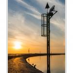 Promenade le long du chenal de la Somme à Saint-Valery, au Cap Hornu alors ques les nuages colorés par le soleil couchant se reflètent dans l'eau. Saison : été - Lieu : Cap Hornu, Saint-Valery-sur-Somme, Baie de Somme, Somme, Picardie, France.
