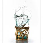 Glaçon qui tombe dans un verre, l'eau déborde et proque des éclaboussures.