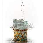 Remplissage d'un verre entourré d'osier avec de l'eau. Le verre déborde et éclabousse.