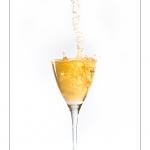 Remplissage d'un verre avec du cidre ou du champagne. Le verre déborde et éclabousse.