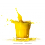 Glaçon qui tombe dans un verre de jus d'orange (boisson jaune) et provoque une éclaboussure.